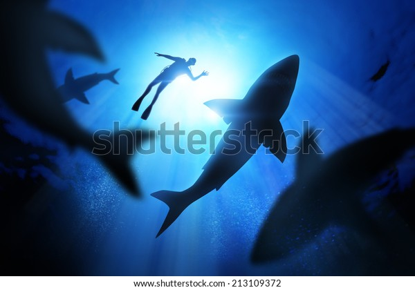 Under the waves a diver with great white sharks.