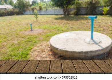 underground cement cylinder of lavatory cesspit in lawn yard (blur background with wood table top for display or montage your product)