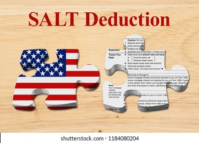 Understanding how the SALT deduction limits affect your taxes, Two puzzle pieces with the flag of the USA and a US Federal tax 1040 income tax form on wood 3D Illustration