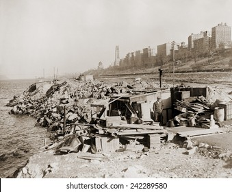 An unemployed a man standing near his hut in a New York City shanty town during the Great Depression. In the background are Upper West Side landmarks, Grant's Tomb and Riverside Church. 1933.