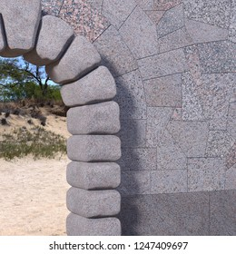 Upper right part of a cyclopean stone gate with granite tiled wall, sand and trees viewed through the opening. 3d render.