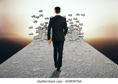 Vagueness concept with businessman walking on road that is breaking into puzzle pieces. Misty landscape background. 3D Rendering