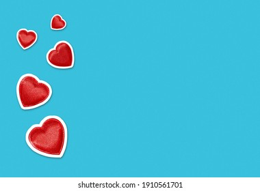 Valentines day background with red heart shape cut outs on bright blue background with plenty of copy space. Magazine collage style love banner