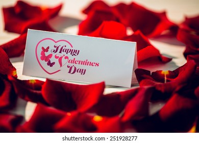 Valentines message against card surrounded by petals