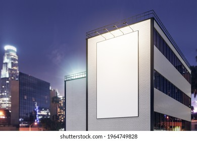 Vertical white blank outdoor billboard with lighting backlights on brick wall of modern building at night city background. 3D rendering, mockup