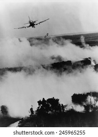 Vietnam War bombing. Two bombs fall from a Vietnamese Air Force A-1E Skyraider over a burning Viet Cong hideout near Cantho, South Viet Nam. 1967.