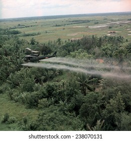 Vietnam War Defoliation Mission a UH- 1D helicopter from the 336th Aviation Company sprays a agent orange on a dense jungle area in the Mekong delta