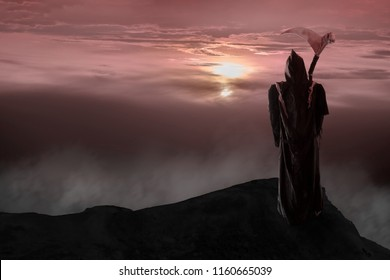 View of grim reaper standing on cliff with twilight background. Grim Reaper, The Death.