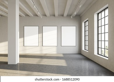 View of three vertical mock up poster frames hanging on wall in sunlit industrial style gallery with columns and concrete floor. Concept of advertising and exhibition. 3d rendering