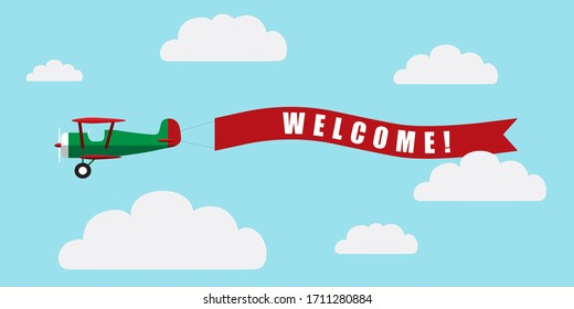 Vintage airplane with banner Welcome on blue sky with clouds background