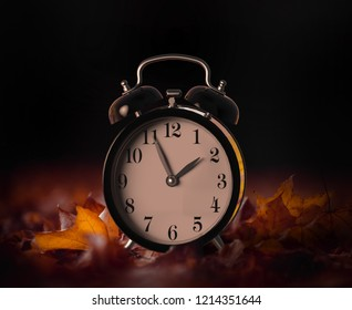 Vintage alarm clock buried underneath colorful fallen autumn leaves with shallow depth of field. Daylight savings time concept with clock hands at almost 2 am, 3D illustration