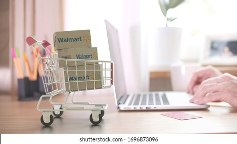 WALMART logo on boxes in shopping cart near the laptop. Editorial online shopping from home 3D rendering