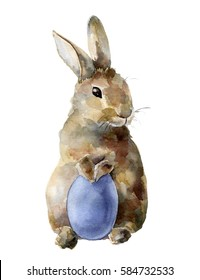 Watercolor Easter bunny with colored egg. Hand painted card with traditional symbols isolated on white background. Cute baby rabbit illustration for design
