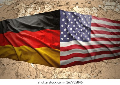 Waving American and German flags on the background of the political map of the world