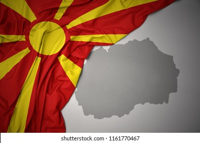 waving colorful national flag of macedonia on a gray map background.3D illustration