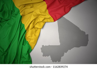 waving colorful national flag of mali on a gray map background. 3D illustration
