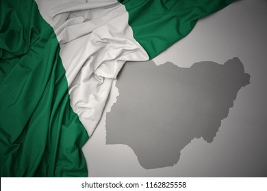 waving colorful national flag of nigeria on a gray map background. 3D illustration
