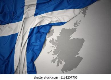 waving colorful national flag of scotland on a gray map background.3D illustration