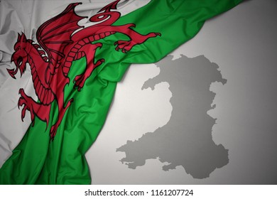 waving colorful national flag of wales on a gray map background.3D illustration