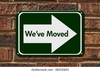 We have Moved Sign,  A green sign with the word We've Moved with an arrow on a brick wall