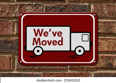We have Moved Sign,  A red sign with the word We've Moved with a truck on a brick wall
