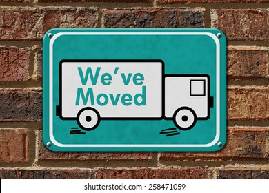We have Moved Sign,  A teal sign with the word We've Moved with a truck on a brick wall