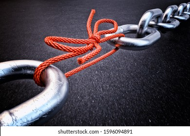 Weakest link, security break fix and strength concept, metallic chain connected by a red knotted rope on black background, 3d illustration