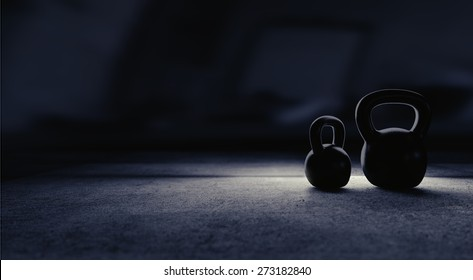 Weight lifting background image with artistic rim lightning on two kettlebells and space for text.
