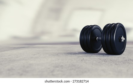 Weight lifting background image with heavy dumbbell and space for text.