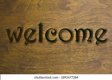Welcome sign set on a wood background. Brown 3D text against wood grain background.