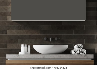 White bathroom sink near a black brick wall with a large mirror hanging above it. Front view. 3d rendering