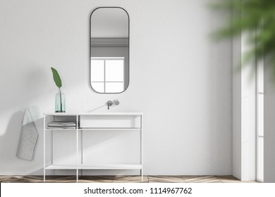 White bathroom sink standing in a Scandinavian style bathroom interior with a narrow vertical horizontal mirror hanging above it. 3d rendering mock up