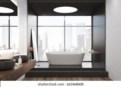 White bathtub is standing on stairs in a black room with a large window and a round ceiling lamp. A mirror on the wall and two sinks. 3d rendering