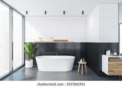 White and black bathroom with white bathtub and deck for towels, grey marble floor. Windows with city view and plant in the corner, 3D rendering no people