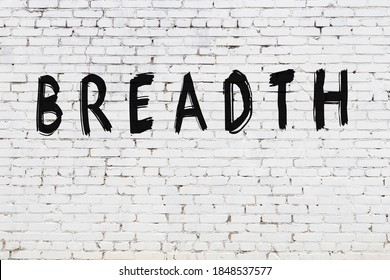 White brick wall with inscription breadth handwritten with black paint