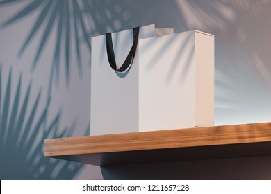 White cardboard box and shopping bag with black handles on wooden shelf with plant shadow on white wall background, 3d rendering.