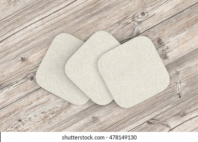 White coasters. Isolated on wood background. 3d render