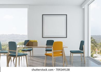 White dining room interior with long wooden and glass table, blue and yellow chairs, a framed square poster and loft windows. 3d rendering mock up
