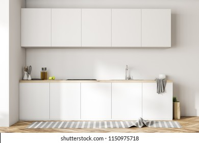 White kitchen counters with a cooker, kitchenware and bottles on them. A row of closets hanging above it in a white room. 3d rendering mock up