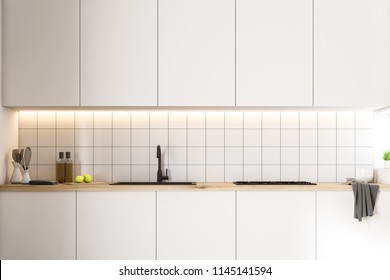 White kitchen countertops with built in appliances standing in a kitchen with white tile walls. Interior design concept. 3d rendering mock up
