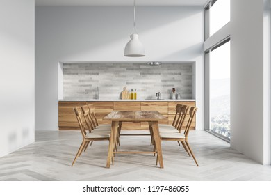 White kitchen and dining room interior with white walls, white wooden floor, wooden countertops and massive table with chairs. 3d rendering