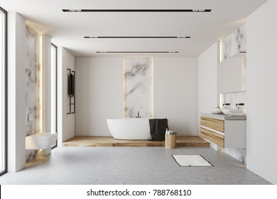 White and marble bathroom interior with a white tub standing on a wooden floor near a chair with self care products. 3d rendering mock up