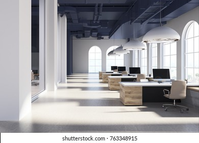 White modern open space office interior with arch like windows, a concrete floor and a row of wooden computer tables. Concept of an open space environment. 3d rendering mock up
