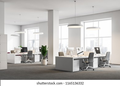 White office corner with gray carpet on the floor, white ceiling lamps and columns and rows of white computer desks. Large windows with a modern cityscape. 3d rendering mock up