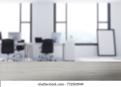 White office interior with a concrete floor, large windows, computer tables, and a framed poster on the floor. 3d rendering mock up blurred
