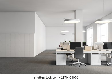 White office interior with gray carpet on the floor, white ceiling lamps and columns and rows of white computer desks. Lockers on the left. 3d rendering mock up