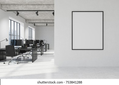 White open space office interior with a concrete floor, two large windows and black wooden desks with computers on them. A vertical poster on a white wall. 3d rendering mock up