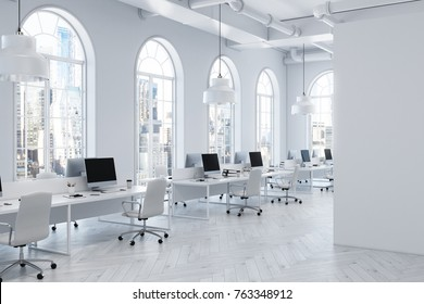 White open space office interior with arch like windows, a concrete floor and a row of computer tables. Side view. 3d rendering mock up