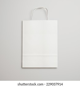 White paper bag with handles on light gray background