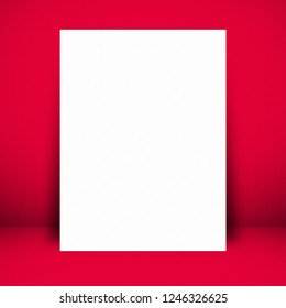 White paper poster lean on red wall background. For text input or according to your design.